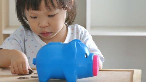 Cute little girl putting money in piggy bank
