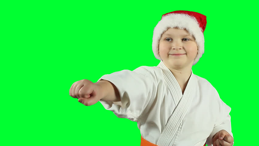 The boy in white kimono and wearing Santa hat doing a karate punch on to the transparent background. PNG+Alpha