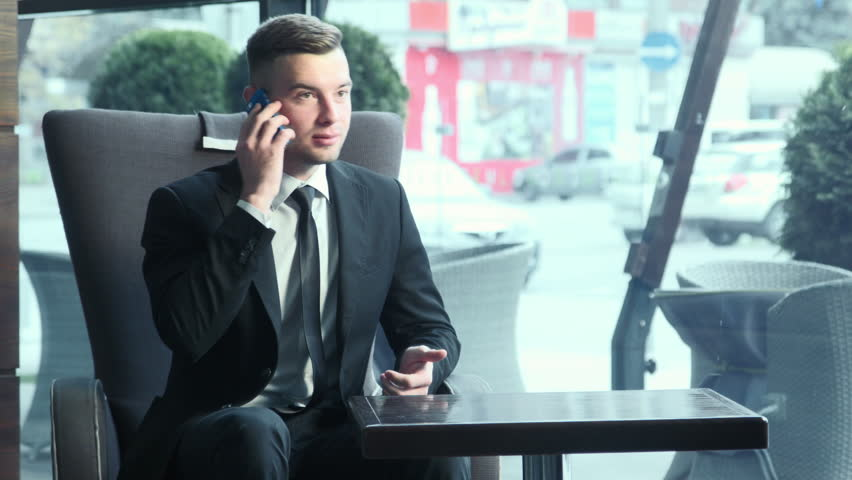 The businessman speaks by phone sitting at table in hotel or business center | Shutterstock HD Video #12358445