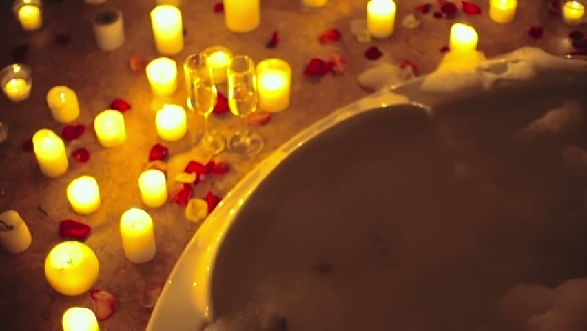 Romantic man giving his girlfriend a head massage in bubble bath in  candlelight