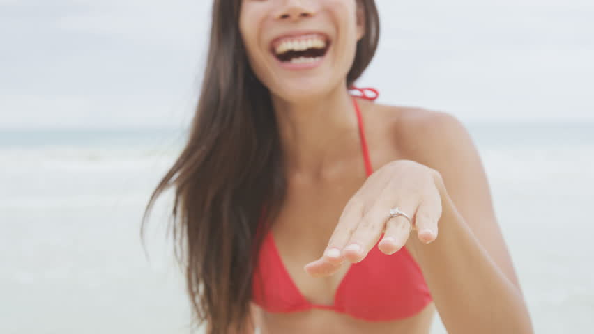 Woman showing Engagement Ring on beach after marriage proposal. Excited happy cute girl in wedding concept on Hawaii laughing having fun in bikini during holiday travel. RED EPIC SLOW MOTION