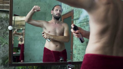 Young man applying antiperspirant on his armpit in bathroom
