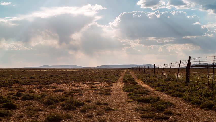 Timelaspe at sunset with sun flare of a Karoo farm landscape with scattered cumulous clouds looking like rain, framed by a fence with a dirt road leading you towards the distant mountains and hills