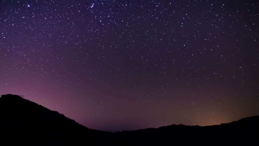 Night time lapse stars passing over mountains and distant ocean