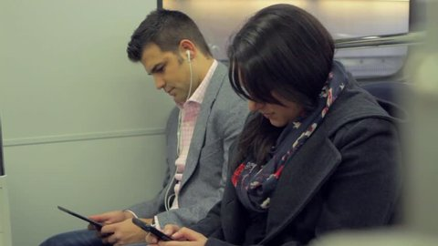 A woman looks up as someone boards the train and a man continues to read on his e-reader