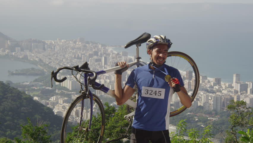 Slow motion bicyclist holding bike and winning medal