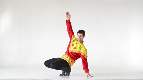 Young man wearing a folk costumes dancing on white background in full length.