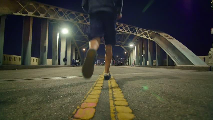 Man in dark hoodie running away in the middle of historic 6th Street Bridge viaduct in Los Angeles. Slow motion.