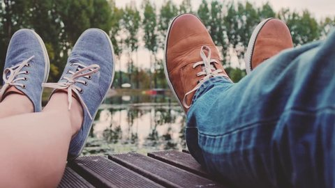 Point Of View: Couple sitting on a wooden jetty playing footsie, close up on modern hipster shoes. 4K Ultra HD. Relaxed time by the lake on a pier. POV: romantic young love by the lakeside. Fashion.
