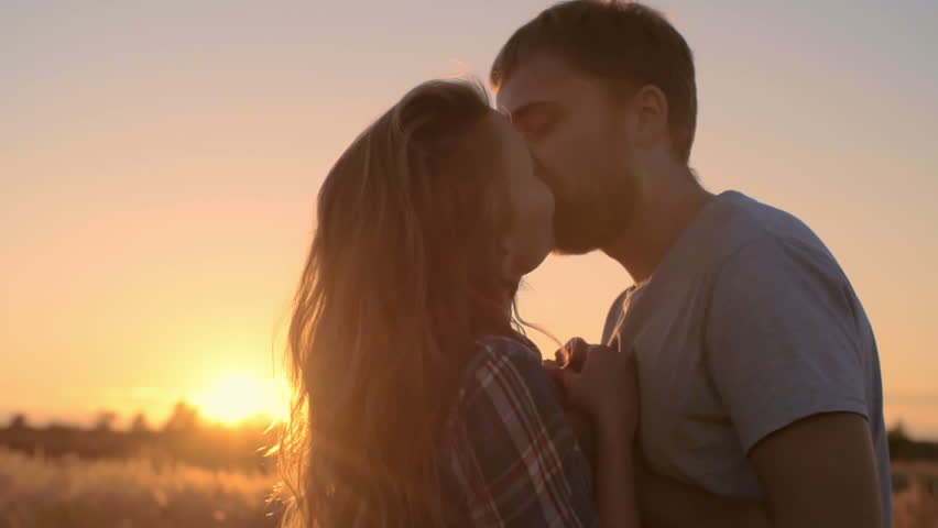 Adorable young couple embracing and kissing tenderly in countryside at sunset