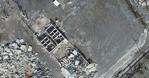 Top aerial view of destroyed town. Cityscape. Demolished neighbourhood, houses transformed into rubble after a natural disaster. Camera moves slowly capturing ruins of the streets.