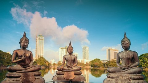 Bronze statues of benevolent Buddhas sitting in meditation on the modern city by the lake background timelapse at sunrise time.