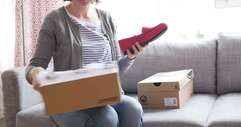 PARIS, FRANCE - Woman unboxing a freshly received box with two smaller boxes bought from Crocs online fashion store