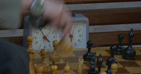 LVIV/UKRAINE - JUL 14 2015: Two Men Are Sitting in Front of Each Other on The Bench, Playing Chess, Turn Chess Clocks on, chess clocks closeup, show 5 and 6, Chess Board Closeup,the players take