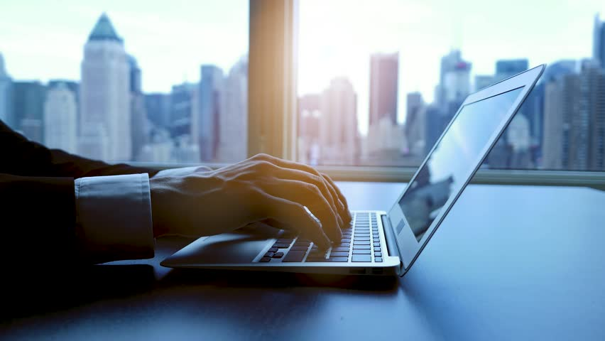 Businessman working on laptop in modern office. urban city skyline background   Shutterstock HD Video #12549425