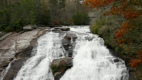 High Falls Waterfall, Dupont State Forest, North Carolina in the Autumn. Tilt downward from covered bridge to pooling water and colorful, fall leaves.