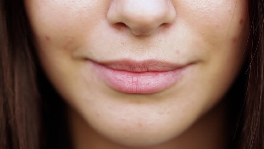 Extreme close up of lips 18-year-old girl with smile. Without lipstick.