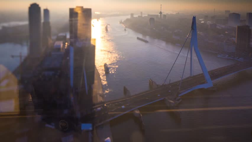 Long exposure static timelapse of the famous erasmus bridge traffic at sunset and with Kop van Zuid and the urban skyline of one of europe's biggest harbours in Rotterdam, the Netherlands