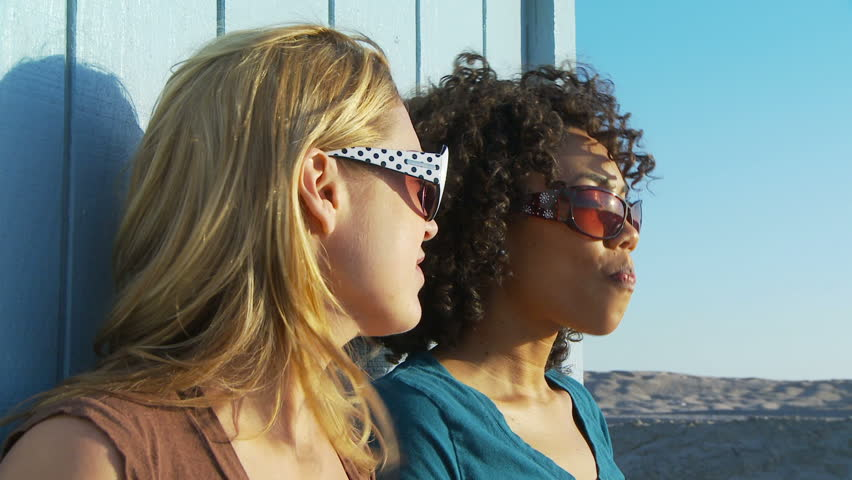 Two women friends in sunglasses blowing bubblegum at the beach