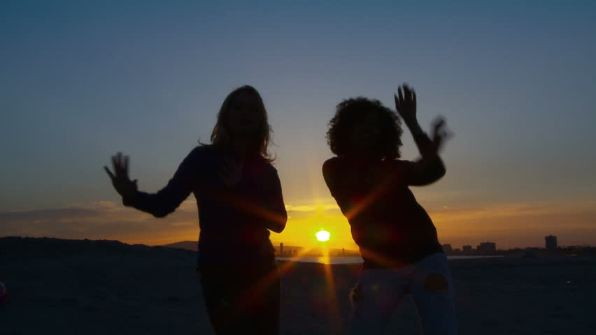 Two women friends dancing on the beach at sunset