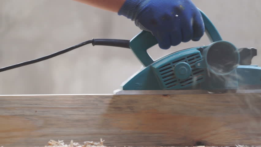 Work carpenter in the workshop. Electric Planer. Treatment of wooden planks electric tool