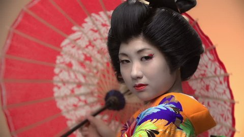 Japanese geisha performer posing in Studio with umbrellas, slow motion