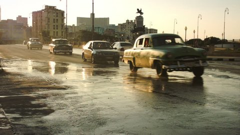 Lots of classic cars driving in golden hour sunset in Havana