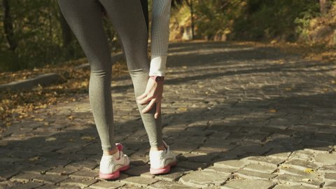 Sport running ankle sprain. Sportswomen touching painful twisted ankle.