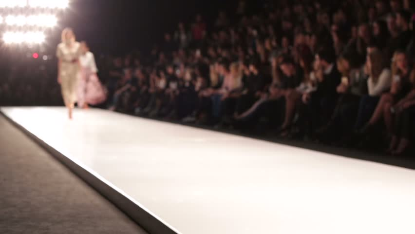 Out of focus background, models walk the runway during fashion show.