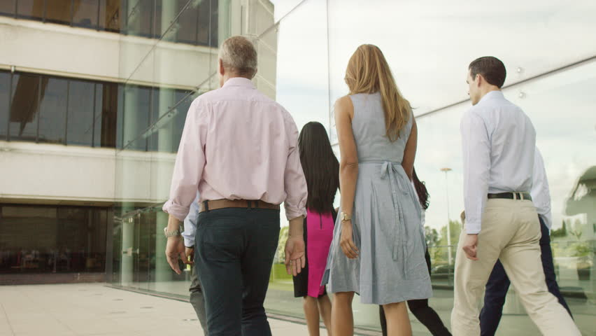 4K Attractive mixed ethnicity business team walking together outside modern glass office building. Shot on RED Epic. | Shutterstock HD Video #12630404