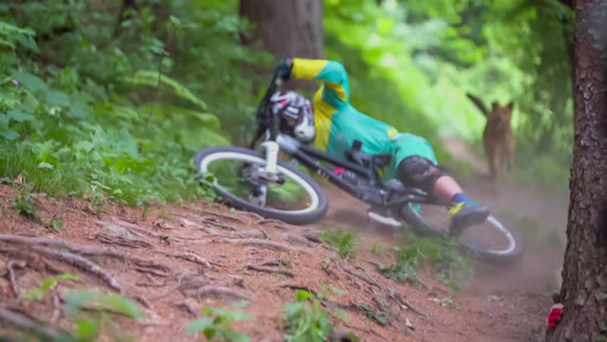 This professional rider is fall down from bike in the middle of very beautiful green nature on countryside.
