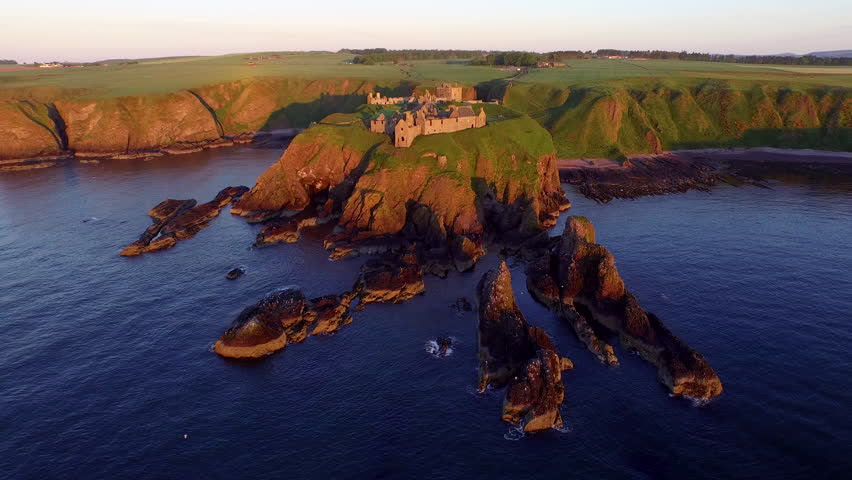 This footage was filmed at Dunnottar Castle (Scotland).. This footage was taken out at sea looking back at the castle. The camera pans around the castle. Strong colors from the sunrise.