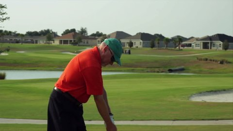 A golfer grabs his lower back and winces in pain during a golf swing.