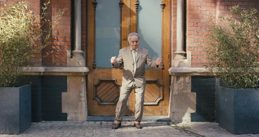 Happy elderly dancer man wearing suit in front of apartment funky street dancing freestyle in the city | Shutterstock Video #12658718