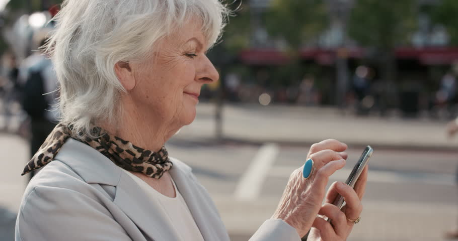 Slow Motion Portrait of happy mature old woman using smart phone sharing social media connection in city real people series