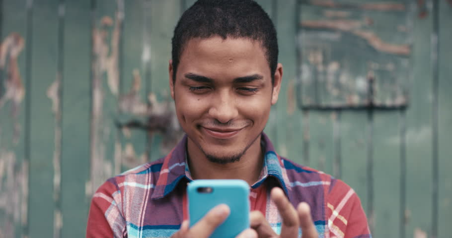 Slow Motion Portrait of mixed race man smiling using smart phone sharing social media connection in the city urban face normal people series