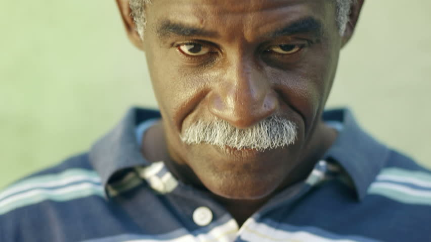 portrait of senior black man with mustache looking at camera against green wall and smiling