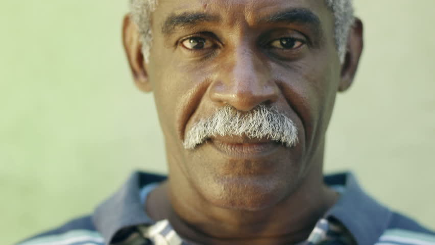 Portrait of old black man with mustache looking at camera against green wall and smiling. Senior african american people