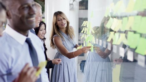 4K Attractive mixed ethnicity business team brainstorming for ideas with sticky notes in modern office. Shot on RED Epic
