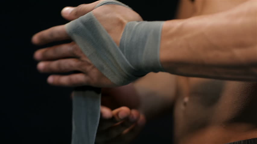 Close up man pulls the belt on the hand before exercise, side view. Muscular man bodybuilder. Man posing on a black background, shows his muscles. Bodybuilding, posing, black background, muscles - the