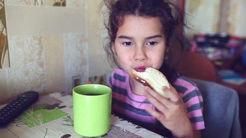 Teen  girl eats bread with butter tea drinkers breakfast