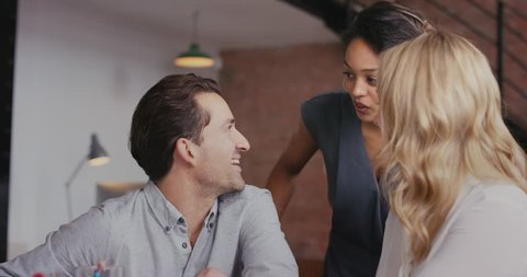 Woman team leader meeting with diverse group of startup business people pointing at computer screen in trendy modern office with red brick walls slow motion