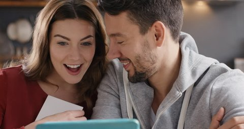 Excited Couple sharing ultrasound pregnancy photo reveal they are pregnant to family over internet using digital tablet