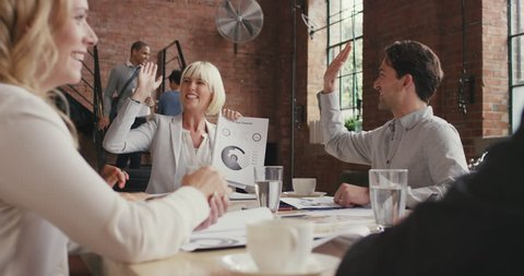 Multi-ethnic business team meeting involved diverse people participating in creative sustainable ideas steadicam shot across boardroom table shared work space high five success