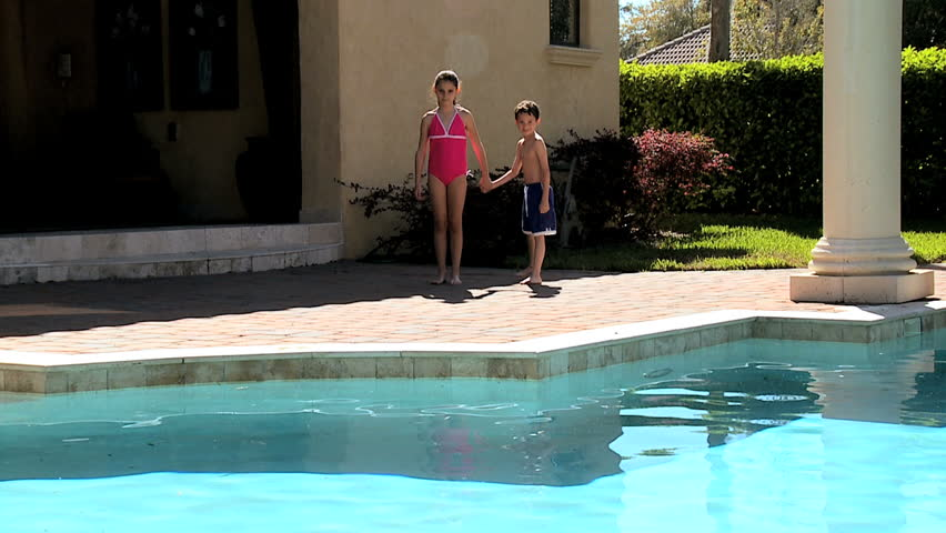 Caucasian siblings jumping into the family swimming pool