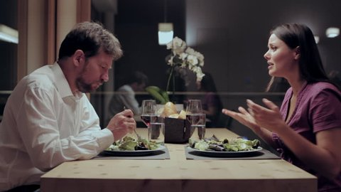 Woman yelling at husband during dinner at home angry