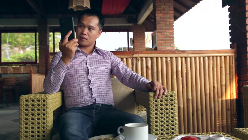 Asian Man talking with mobile phone with angry face expression outdoor