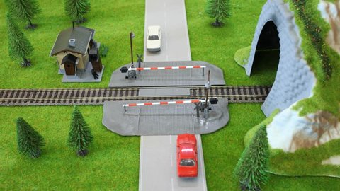 Model of train enters a tunnel, the cars passed him on crossing. Stop motion.