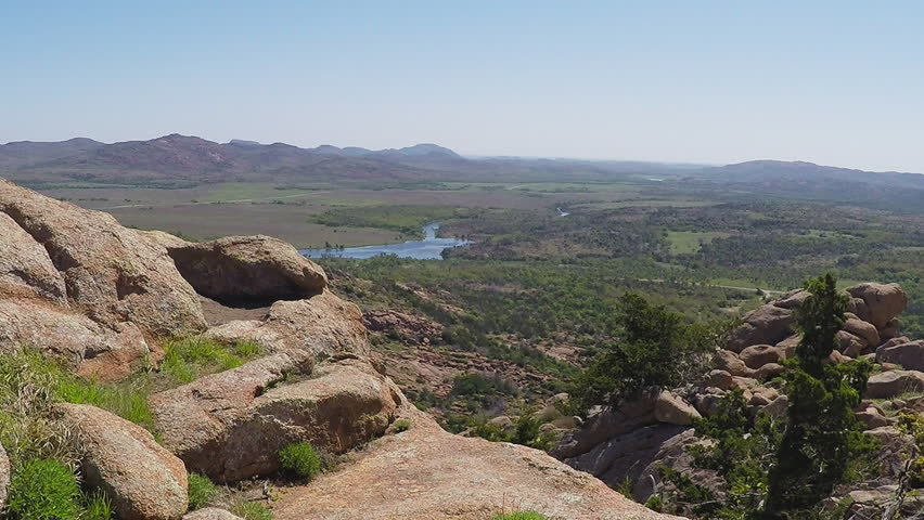 LAWTON, OK/USA: May 2, 2015- A scenic shot from a mountaintop of a green valley with a river running through it in the Wichita Mountains Nature Reserve near Lawton, Oklahoma.
