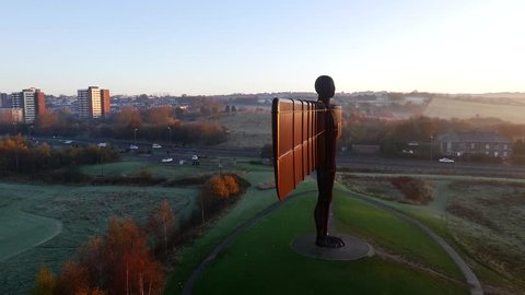 Drone / aerial shot flying around the side revealing the front of the Angel Of The North in the North of England with traffic driving down surrounding roads. Shot September 2014.
